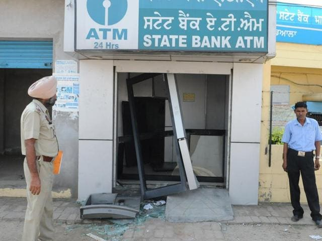 The ATM machine which was found in the field of Dheriya village near Nakodar being inspected by a finger print expert.