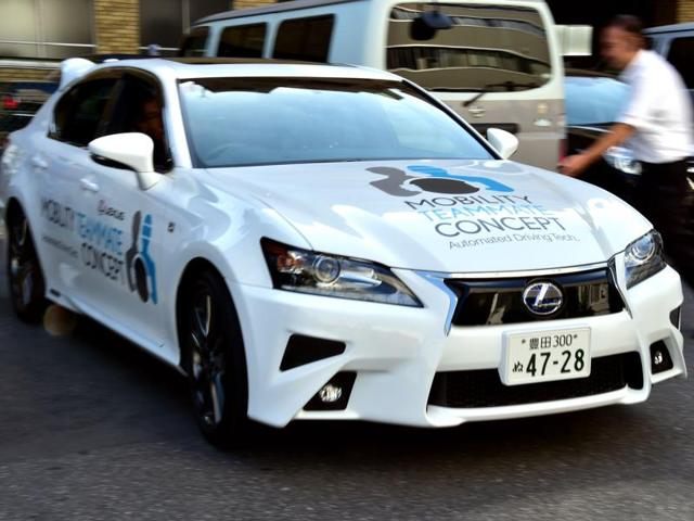 Visitors look at Japan's auto giant Toyota Lexus GS450h , a self-driven car in Tokyo on Tuesday. Toyota is expecting to commercialise autonomous vehicles before the Tokyo Olympics in 2020.