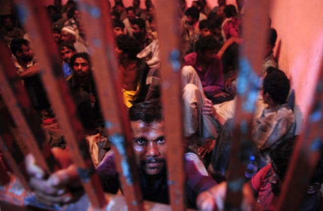 Arrested Indian fishermen gather in a police lock up in Karachi on October 4, 2015.