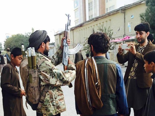 A Taliban fighter (2nd L) poses for a photo at the main square, a day after the insurgents took control of the strategic northern city of Kunduz September 29, 2015.