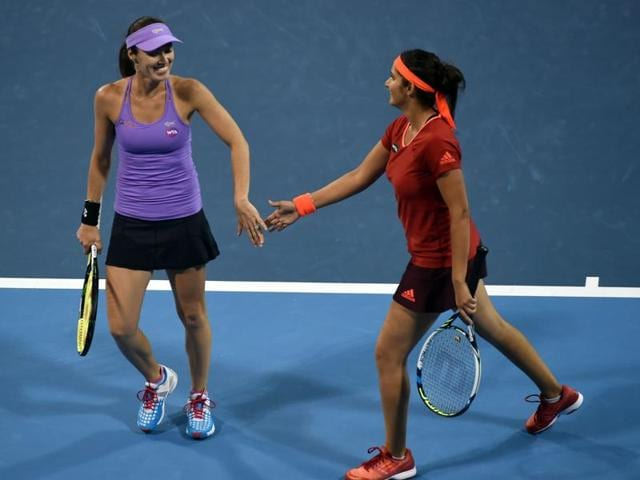 Sania Mirza, right, of India celebrates winning a point with Martina Hingis of Switzerland during the second-round women's doubles match against Sara Errani and Flavia Pennetta of Italy at the China Open in Beijing, on October 7, 2015.