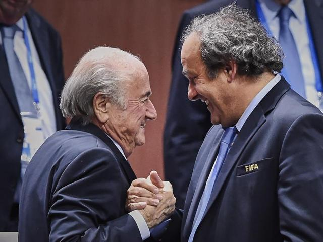 FIFA president Sepp Blatter (foreground-L) shaking hands with UEFA president Michel Platini in Zurich in this file photo. A FIFA ethics watchdog on October 8, 2015 Blatter and Platini for 90 days after they were named in a Swiss corruption case.