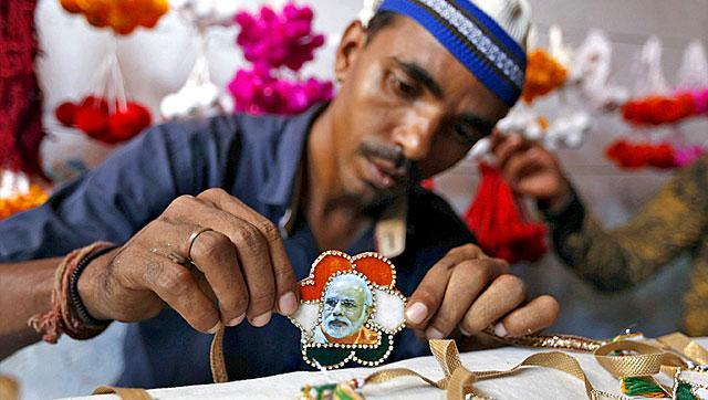 """A Muslim artisan displays a """"Rakhi"""" or traditional Indian sacred thread, featuring India's Prime Minister Narendra Modi after giving it the finishing touches inside a workshop in Ahmedabad. During Raksha Bandhan, a sister ties a Rakhi on her brother's wrist to ask him for her protection."""