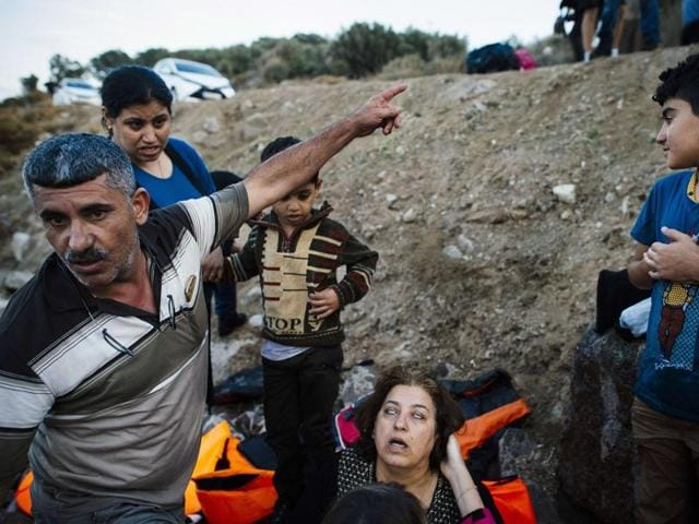 A man looks for medical care for his wife (C) as they arrive with other refugees and migrants on the Greek island of Lesbos after crossing the Aegean Sea from Turkey.