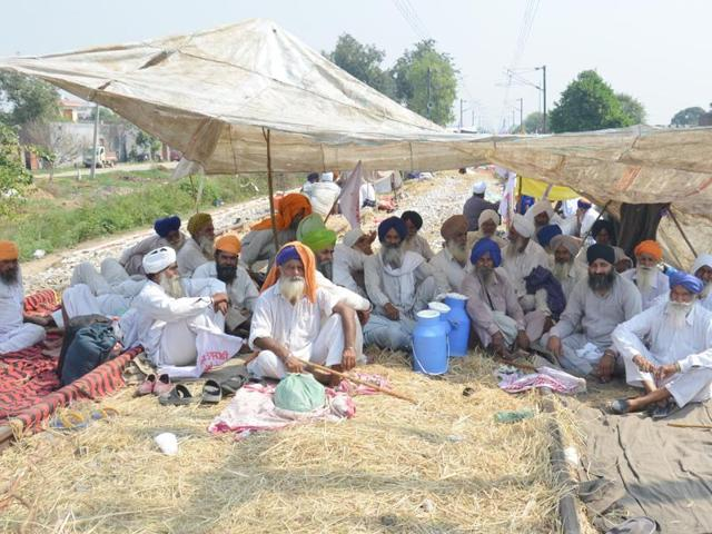 Farmers block train tracks during day three of their protest against the central and Punjab government's allegedly anti-farmer policies at Muchhal village near Amritsar on Friday.