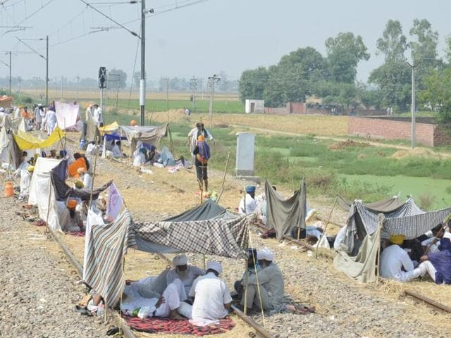 Farmers block train tracks during the third day of their protest against the central and Punjab government's anti-farmer policies at Muchhal village near Tangra ,28 kms from Amritsar on Friday .