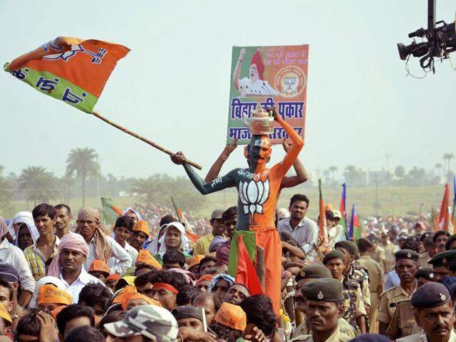 A BJP supporter waves the party flag during an election campaign rally addressed by Prime Minister Narendra Modi at Banka in Bihar.
