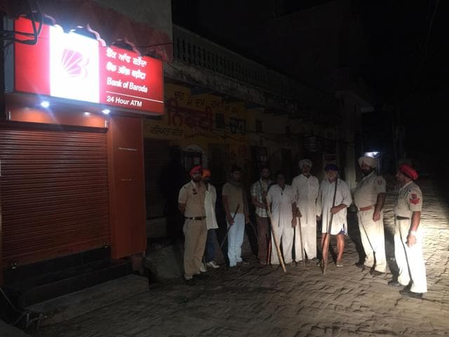 Cops along with villagers outside an ATM kiosk in Phillaur.