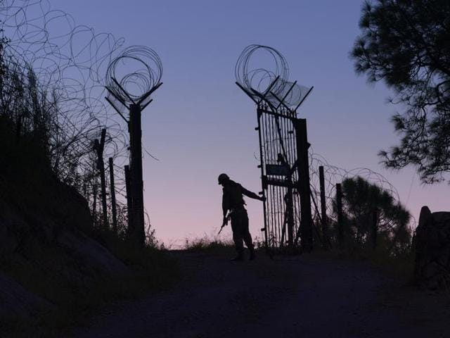 An Indian Army soldier closes the gates on the fence near the LoC separating India and Pakistan in Barasingha area near Bhimber Gali.