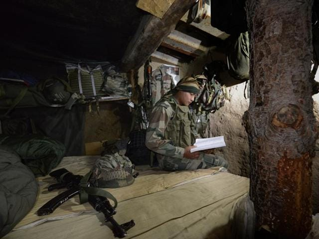 Indian Army Rifleman Anurag Thapa studies in his bunker in a forward post at the India-Pakistan LOC in Saujian area near Poonch.