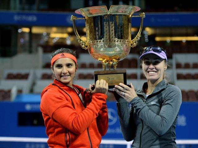 Martina Hingis (R) of Switzerland and partner Sania Mirza of India take photo with the trophy after winning their women's doubles final match against Yung-Jan Chan of Taiwan and partner Hao-Ching Chan of Taiwan at the China Open tennis tournament in Beijing.