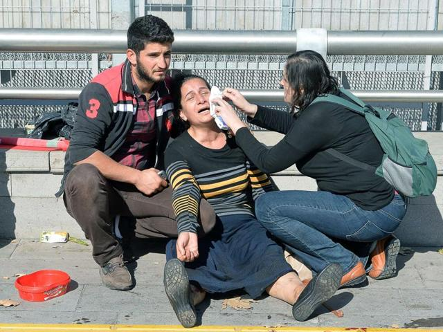 A woman is helped following an explosion at the main train station in Turkey's capital Ankara, on October 10, 2015.