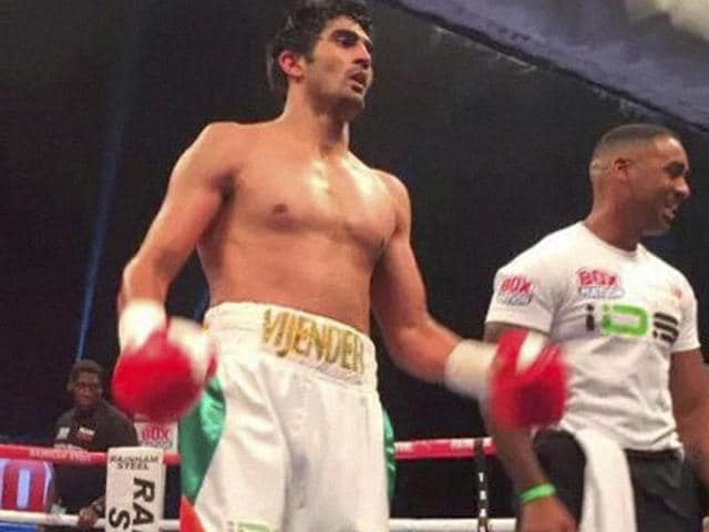 Indian boxer Vijender Singh celebrates after winning the match against England's Sonny Whiting.