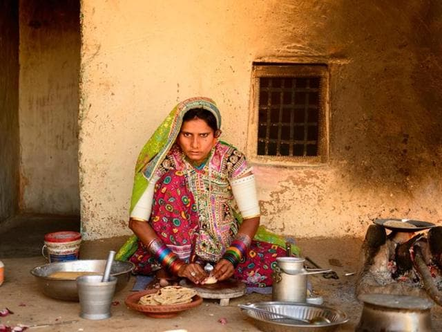 A file photo of a woman cooking in traditional wood fire kitchen in Gujarat.