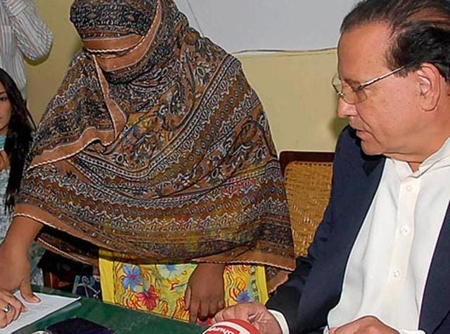 A file photograph shows Pakistani Punjab governor Salman Taseer (R). Taseer was murdered in 2011 for opposing Pakistan's blasphemy laws