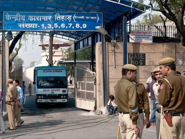 Policemen stand guard as an ambulance leaves the main entrance of Tihar Jail in New Delhi.