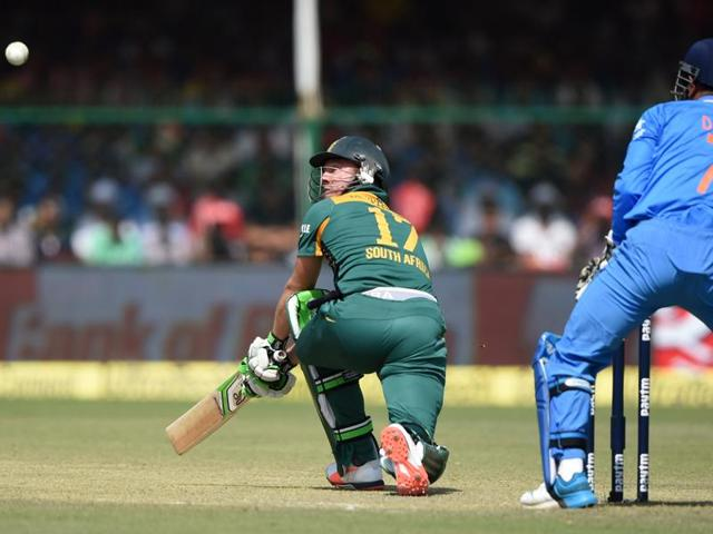 India's captain Mahendra Singh Dhoni (R) looks on as South Africa's captain AB de Villiers plays a shot during the first one day international (ODI) cricket match between India and South Africa at Green Park Stadium in Kanpur.