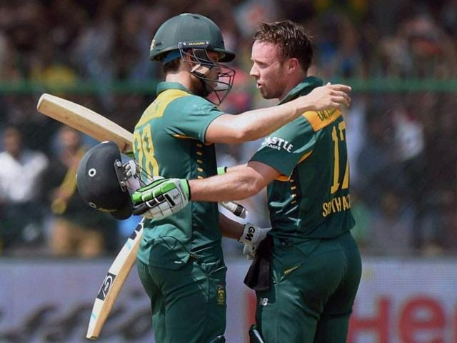 AB De Villiers, right, hugs Farhaan Behardien after completing his century.