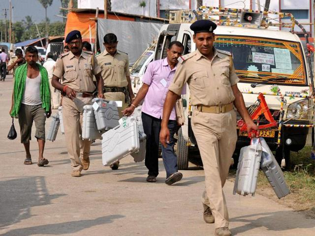Police personnel carry EVM machines to polling booths ahead of the 1st phase of Bihar assembly polls in Bhagalpur.
