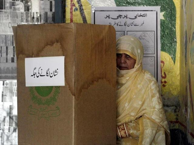 A woman stands in a voting booth as she prepares her ballot for the by-election of a seat in the national assembly in Lahore.