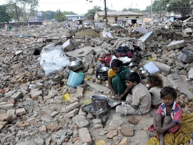 A family cooks food on the rubble of their demolished house in CP Shekhar Nagar on Saturday.