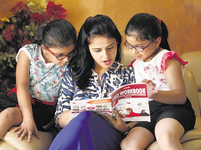 New Delhi, India - Oct. 9, 2015:case study of a SHikha Gupta studying reading story book to her twin Daughters Ania and Kyra who underwent surgery to correct her vision, at Her house in Faridabad in New Delhi, India, on Friday, October 9, 2015. (Photo by Raj K Raj/ Hindustan Times) to go Rhythma with story