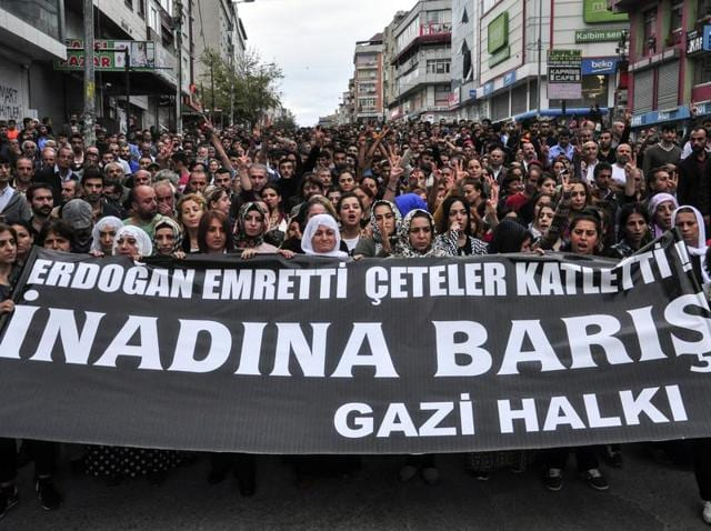 People hold a banner that reads
