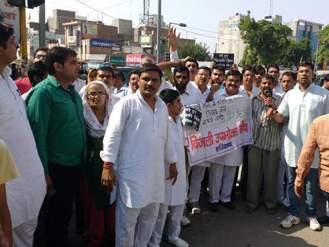 Sangarsh samiti workers staging a protest and shouting slogans against the recent hike in power tariff, in Hisar on Monday.