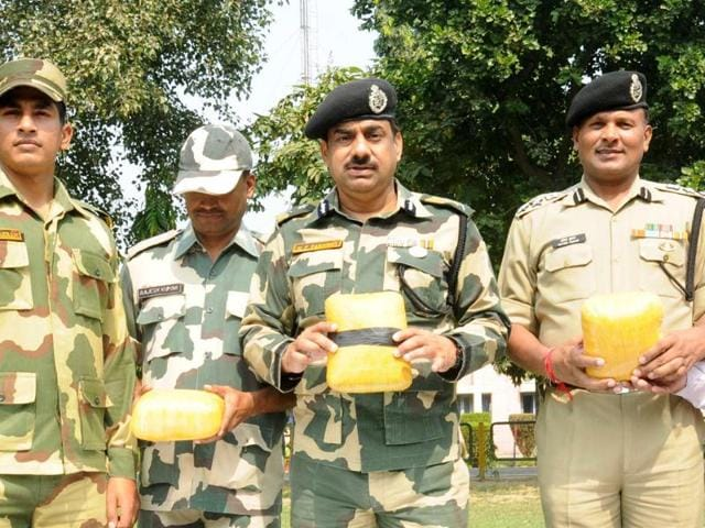BSF DIG MF Farooqui (centre) along with BSF jawans displaying the heroin seized near the Indo-Pak border.