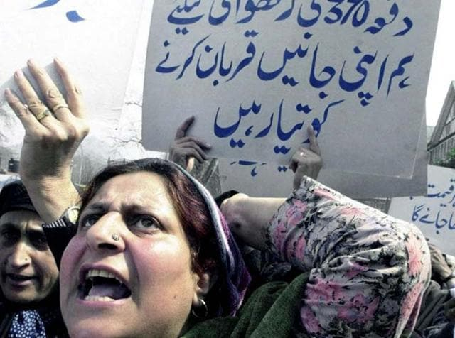 A Kashmiri woman displays a placard reading 'We will preserve article 370 at all costs' during a march in Srinagar.