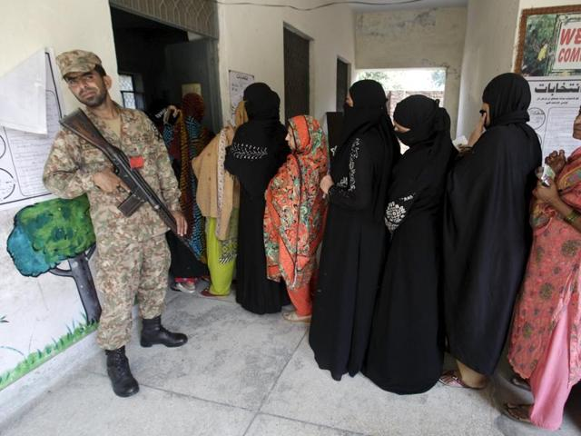 An army soldier stands guard as women line up to vote in the by-election of a seat in the National Assembly, in Lahore, Pakistan October 11, 2015.