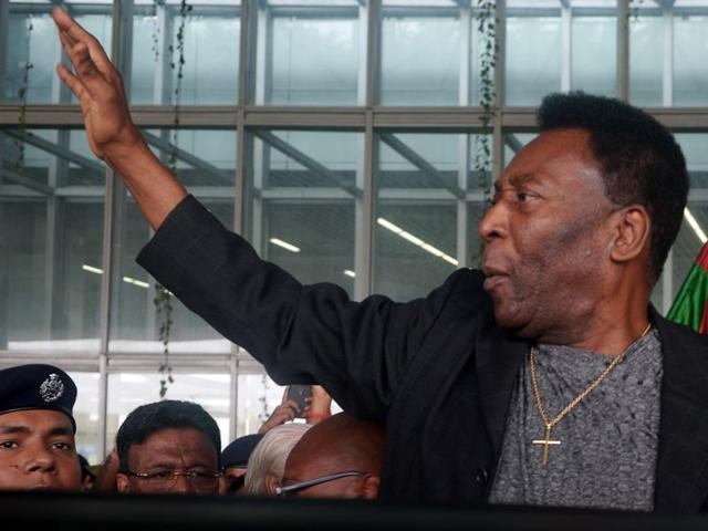 Pele waves to fans after arriving at the Taj hotel in Kolkata for a three-day visit to the city, on October 11, 2015.