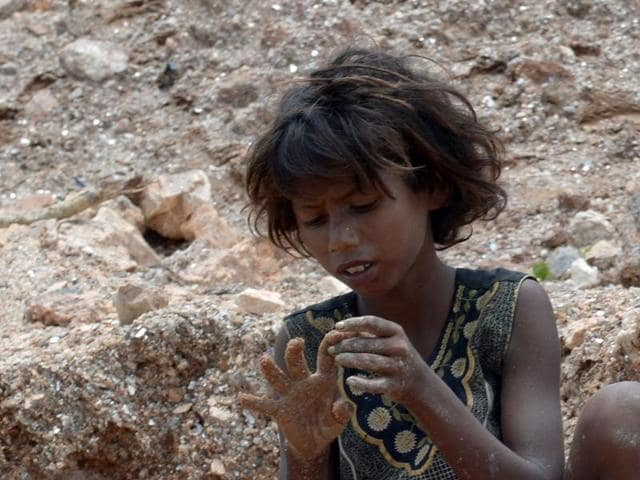 Deaf  child labourer Nagina looks at her finger after hitting it with a hammer while collecting mica at a scrap mine in Koderma district, Jharkhand