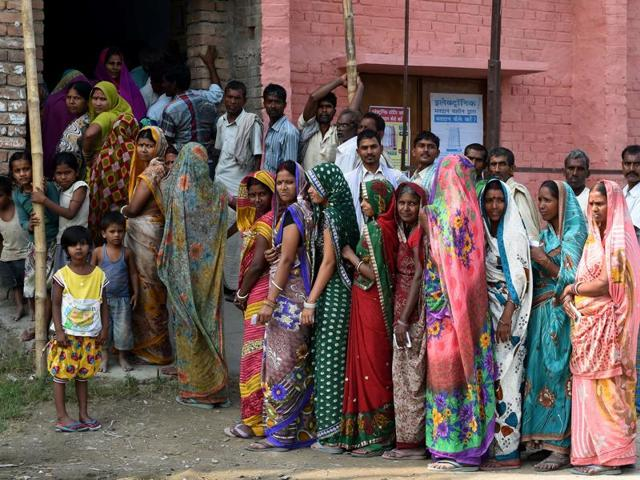 Voters assemble to cast their votes at a centre in the village of Banbira in Samastipur district on October 12, 2015.