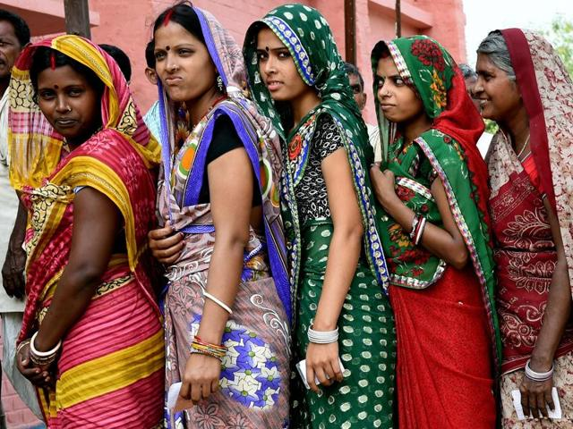 Voters queue to cast their ballots at a voting centre in the village of Banbira in Samastipur district.