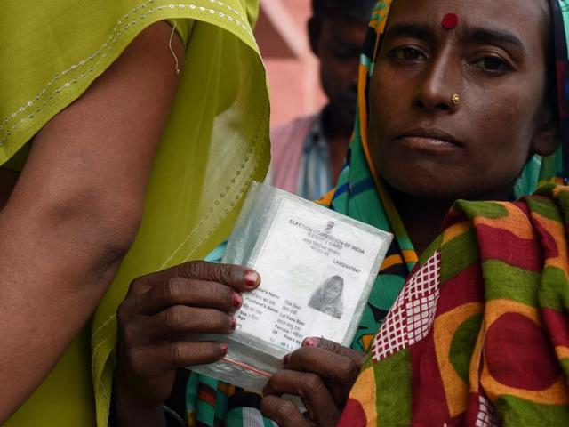 A voter holds up her voting card before casting her ballot at a voting centre in Samastipur .