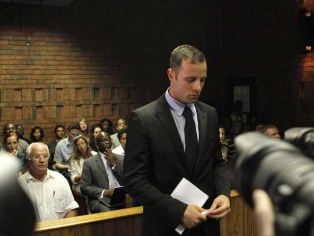Oscar Pistorius stands in the dock during a break in court proceedings at the Pretoria Magistrates court.