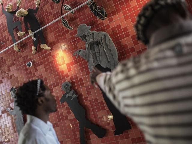 South African artist Lehlohonolo Mkhasibe (R) points at a collective artwork done for the Soweto Theatre in Soweto, South Africa. He is a member of Ubuhle Bobuntu (