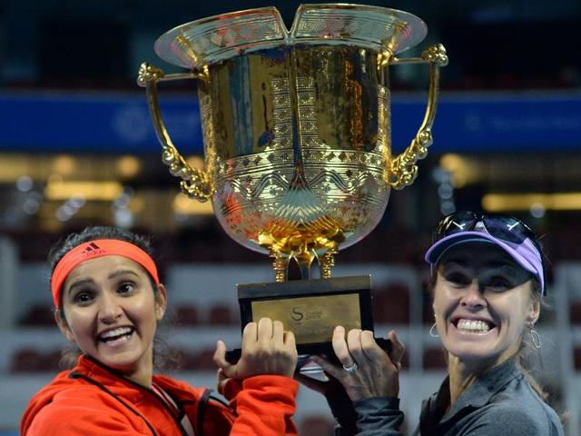 Martina Hingis, right, and Sania Mirza celebrate with the trophy after winning the final of the China Open against Taiwan's Yung-Jan Chan and partner Hao-Ching Chan in Beijing, on October 10, 2015.