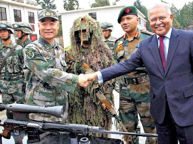 Lt Gen Zhou Xiaozhou shakes hands with Indian Ambassador Ashok K Kantha at Kunming Military Academy in Yunnan on Monday.