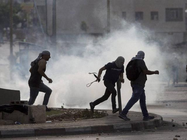 Palestinians run from tear gas during clashes with Israeli troops near Ramallah, West Bank.