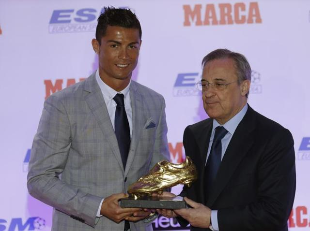 Real Madrid's forward Cristiano Ronaldo poses alongside club President Florentino Perez with the Golden Boot award for scoring the most goals in Europe's domestic leagues last season.