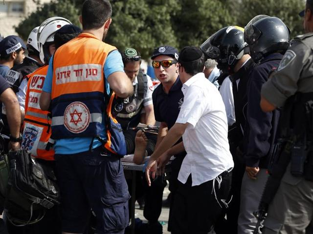 Israeli medics wheel away an injured female Palestinian attacker (C) on a stretcher in Jerusalem on October 12, 2015, following a stabbing attack Israeli police said she carried out near the police headquarters in the holy city.