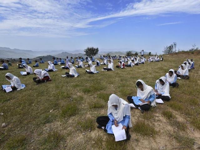 Students of the army-run Pinewood School in Hamirpur area of Bhimber Gali write an exam in open ground, with hills in PoK in the backdrop.