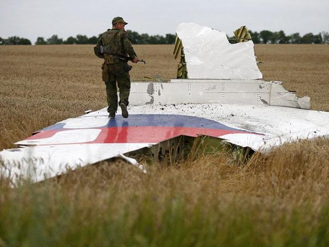 An armed pro-Russian separatist stands on part of the wreckage of the Malaysia Airlines Boeing 777 plane after it crashed in the Donetsk region, Ukraine.