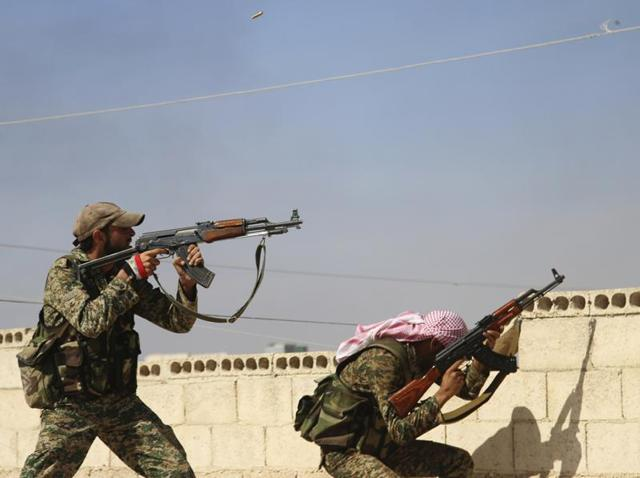 In this photo taken on Sunday, October 11, 2015, Syrian soldiers fire repelling an attack in Achan, Hama province.