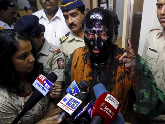 Sudheendra Kulkarni, chairman of the Observer Research Foundation Mumbai, with his face smeared with black ink, speaks to journalists in Mumbai.