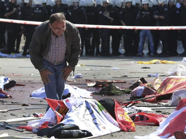 A man stands over the body of a victim at the scene of an explosion in Ankara, Turkey. The two bomb explosions targeting a peace rally in the capital Ankara has killed dozens of people and injured scores of others.