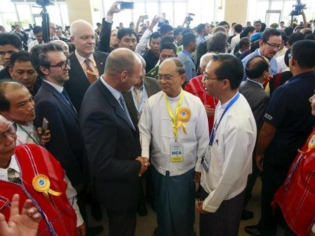 Myanmar's President Thein Sein (with yellow ribbon) greets international witnesses after the signing ceremony of the Nationwide Ceasefire Agreement (NCA) in Naypyitaw, Myanmar.