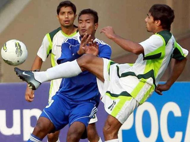 A member of the Nepal men's football team (blue) in action during a South Asian Football Confederation Championship match against Pakistan.